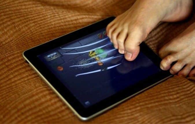 Лю Вей пользуется планшетом используя пальцы ног